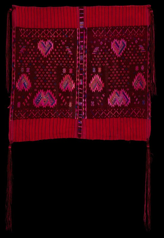 two red panels with blue stripes, sewn together; central dark purple blocks with geometric circles, X's, chevrons and zigzags in pinks, blues and gold; long purple tassels at corners