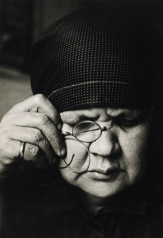 head shot portrait of a woman holding eyeglasses in proper right hand; ring on little finger