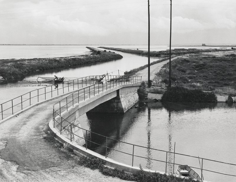 curved bridge foregrond; fisherman tending nets left center ground