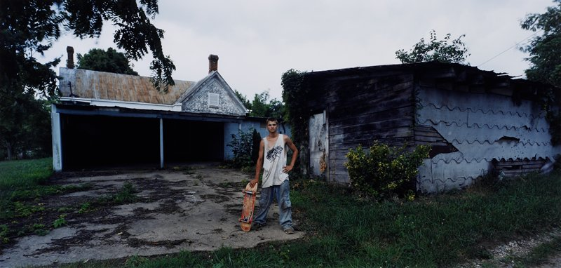 boy at center of image, wearing baggy, dirty jeans and sleeveless shirt, leaning on a skateboard; shed at right, abandoned building with carport or porch at left