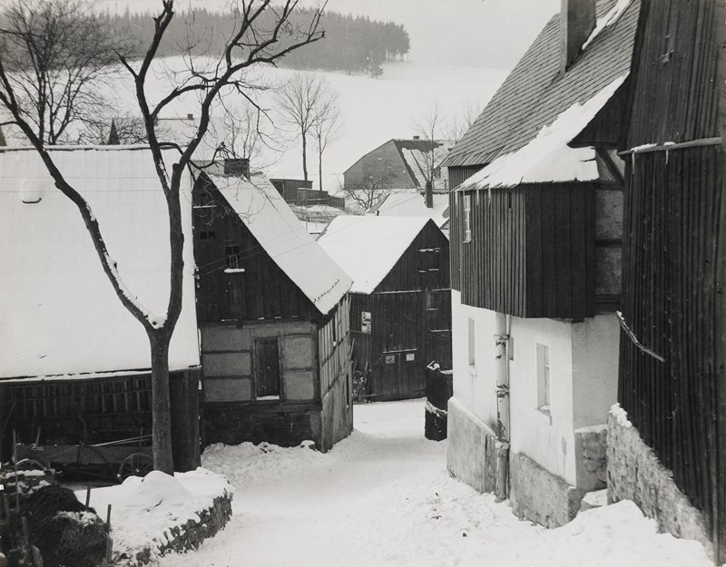 village street, snow-covered; roofs of buildings snowy; hazy countryside in background, rolling hills and trees
