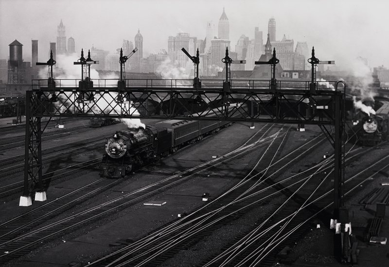 railroad yards; train below signal bridge, several other trains less visible; Manhattan skyline in background