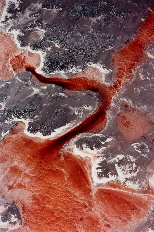 "red ""stream/lake"" with grey and white ""islands""; surface appears rough"