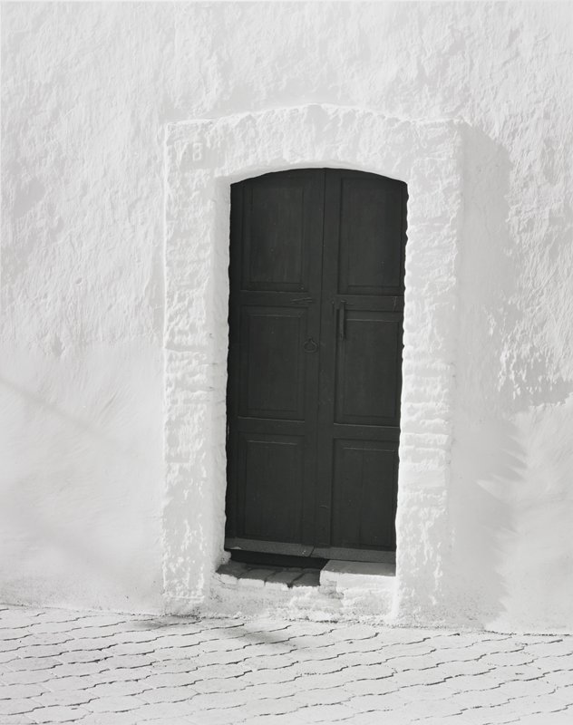 black door in white heavily textured frame; wall smooth below and rough above; brick(?) street