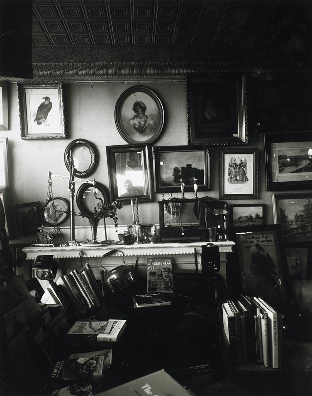 dim interior; books stacked on chairs in foreground; scales, candlesticks and other objects on a mantle; old pictures of bird, ladies and landscapes, and empty frames, on wall