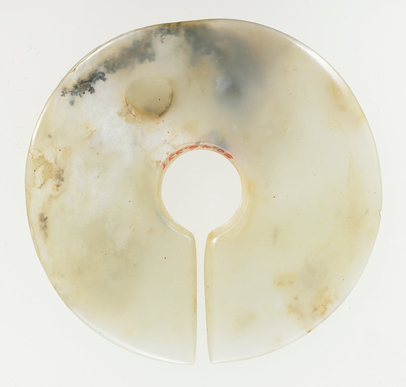plain surface; translucent white jade with opaque white marks of calcification. The disk shaped object is often identified as a 'chueh'.