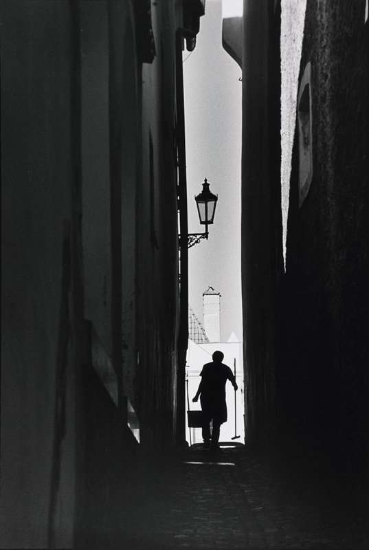 narrow alley; man with pail and brush with back to camera walking toward white building at end of alley