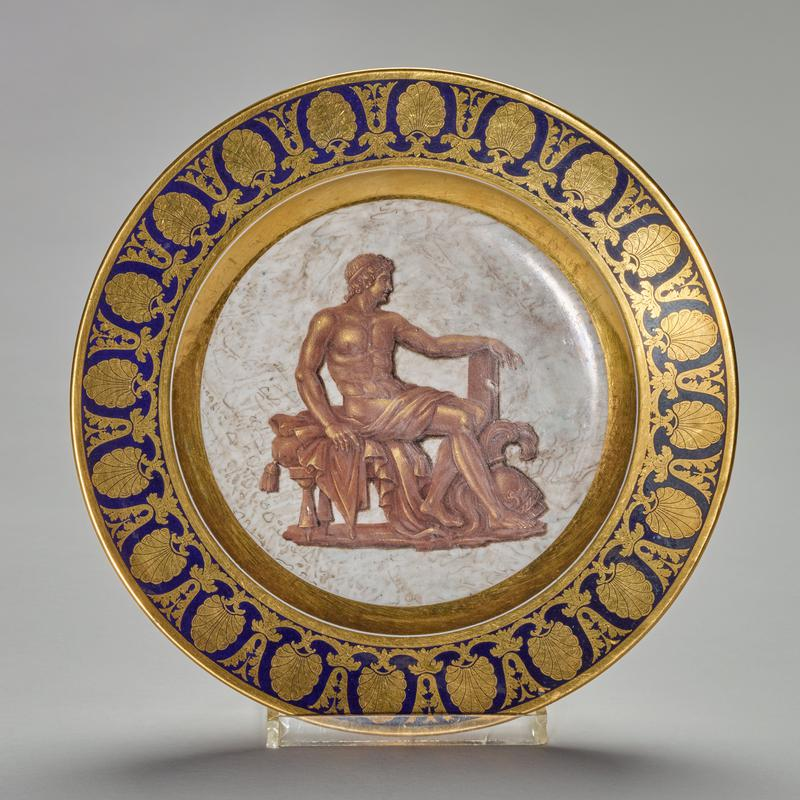 plate, ceramic-porcelain, dark blue with gold border, brown and gold seated figure with helmet at his feet in center agianst a mottled ground, French, XIXc cat. card dims H 1-1/4 x diam 9-1/2' Holiday Traditions, French Room. Part of a dessert service that has been attributed to Pièrre André Le Guay (active 1773-1817) and Joseph Leopold Weydinger (active 1778-1829)