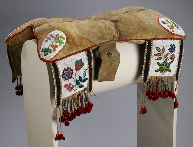 padded saddle cover with ovoid beaded medallion in each corner-white ground with leaves and flowers, trimmed in red fabric; red wool stitching around edges; four decorative flaps at corners-white beaded ground with multicolored beaded flowers and leaves; flaps have red wool tassels with grey, brown and clear beads on fringe