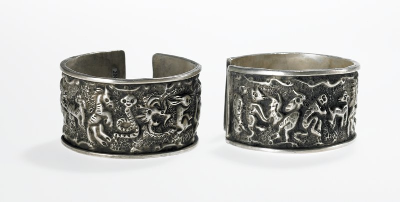 bracelet, one of a pair, cuff style, rellief animals: rabbits, dog or wolf, snakes, horse, monkeys and rooster; top decorative raised border band