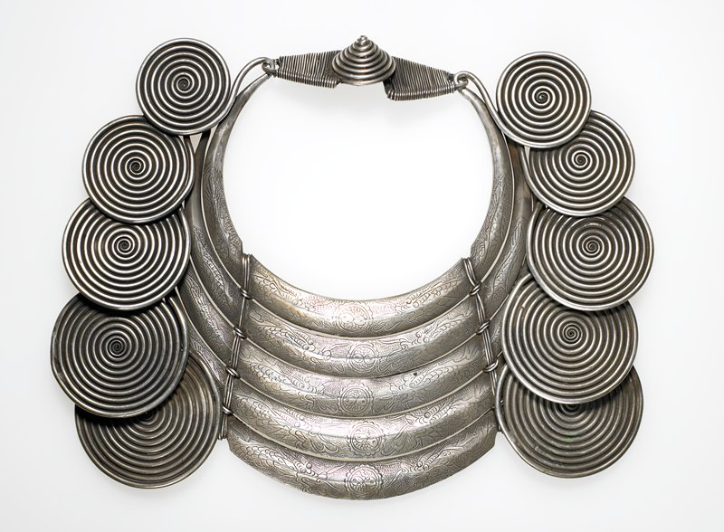 torque with five flat rings; each ring ends with an ever-increasing curlicue--thus there are five graduated curlicues on each side; the rings are held together by wire wrapped on either side of the center; connecting piece made of large wire wrapped by small wire; one large cone decorates the spot where the two connecting pieces latch; rings decorated with medallion in middle and dragons on either sides