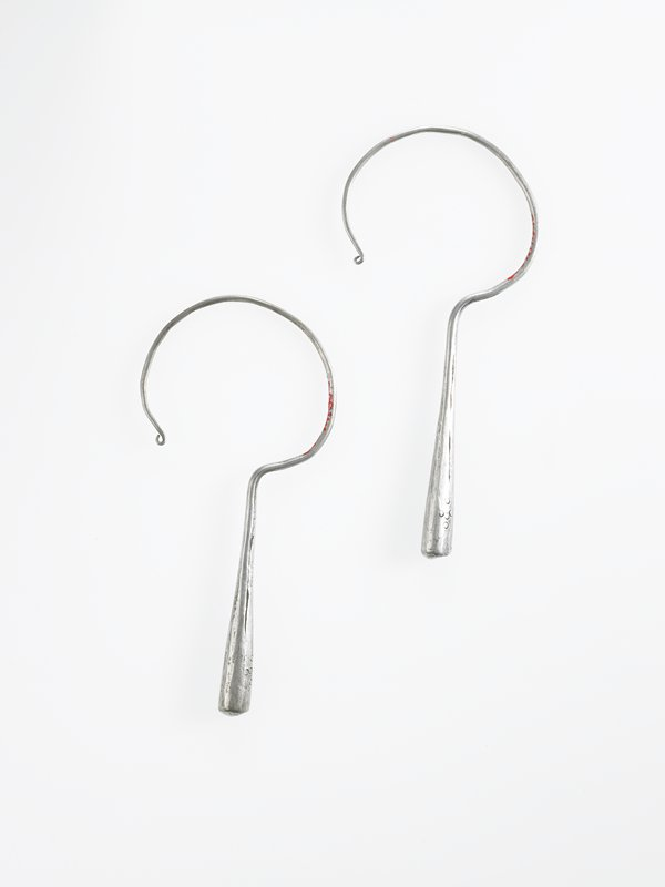 made from a single silver wire, one end is rounded and thickens into a straight teardrop; teardrop is decorated with pattern of four etched circles on two sides; end is rounded