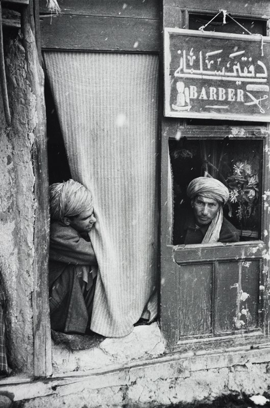 "two men wearing turbans; man at R looks out an open panel in a door, under a sign reading ""BARBER"" in two languages, with images of a razor and brush, comb and scissors; man at L looks out from behind a curtain covering opening to L of door"