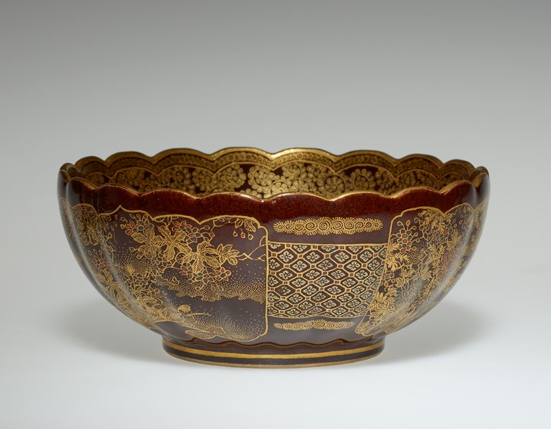 scalloped edge; fluted exterior; enamel and gilt; brown ground; landscapes in cartouches on exterior; fan design at interior with two cartouches with picnickers and wagon in landscapes