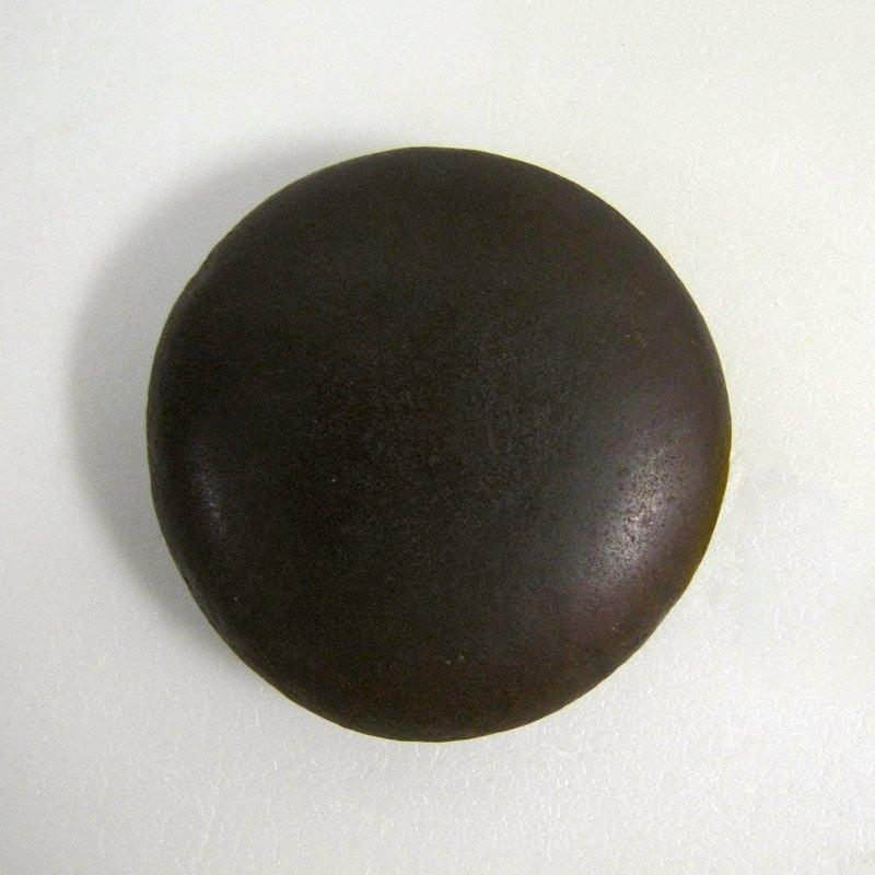 flat, round stone; dark brown