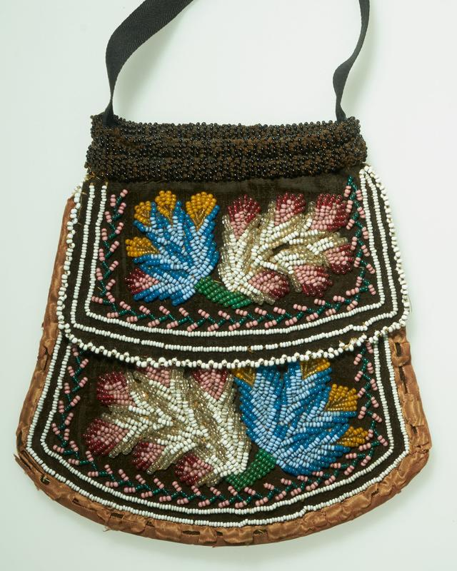 small bag with black twill strap; central open pouch; flap on each side covers pocket on each side; ribbon edging; dark brown velvet with beaded leaf designs-same on each side