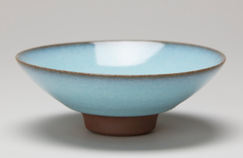 thick base on tall ring foot; saucer-shaped; brown clay; blue with brown at rim