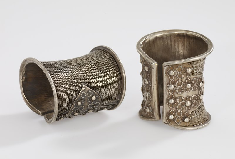 bracelet cuff where the opening is on the top; large smooth rims running along all the edges; majority of the body is covered in thin, braided wire; flat metal sheet is wrapped along each edge of the slit; two rows of flowers run vertically along the sheet; sheet comes to a rounded point where there are two flowers; flowers have curved wire in between them