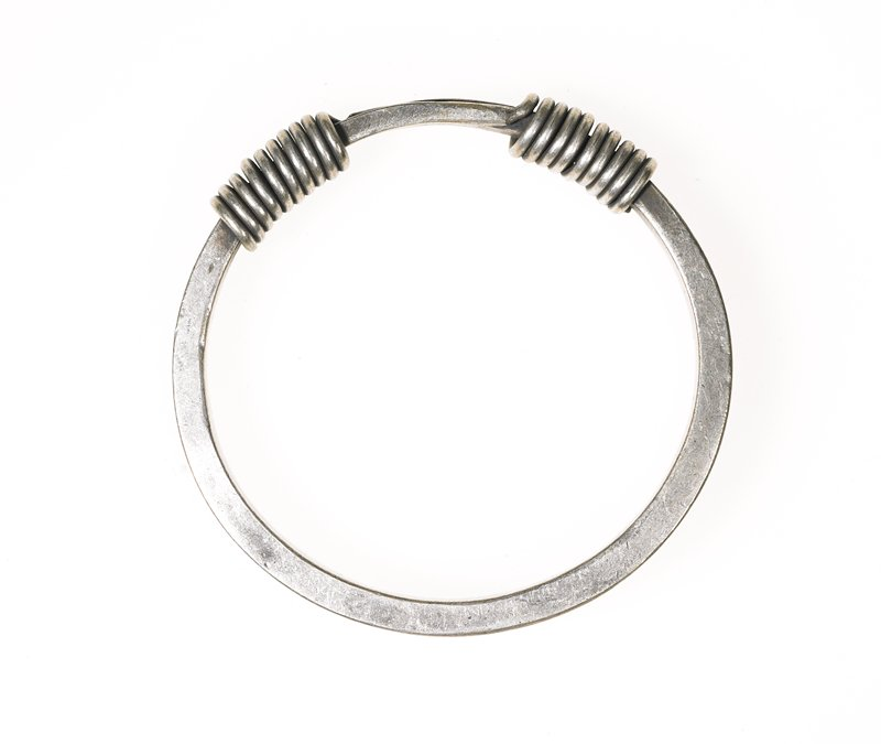 one of a pair of bracelets; main body is a hoop made from thick, square wire; ends are wrapped in thinner circular wire