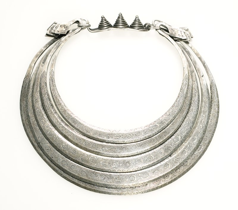 torque made from five consecutive rings of flat, solid silver; rings end by curving over themselves; each ends with a decorated, diamond-shaped piece; connecting piece is decorated with three wire cones; rings are decorated with triangle and line border on both sides; floral pattern decorates the center of each ring