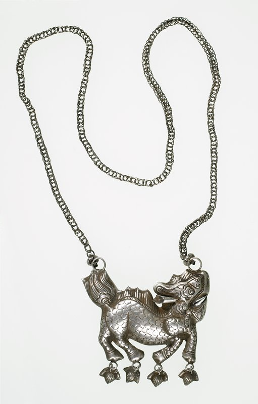 necklace with long, square chain; chain has a small wire flower at each end; wire flowers are linked to a hollow, pressed, horse-like creature; leaf-like objects dangle from each hoop