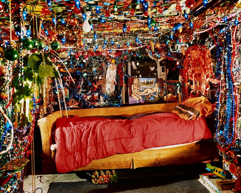 gold couch with red sleeping bag and orange, brown and white pillow in a niche surrounded by Christmas lights, garland, beads; painting of two nudes behind couch