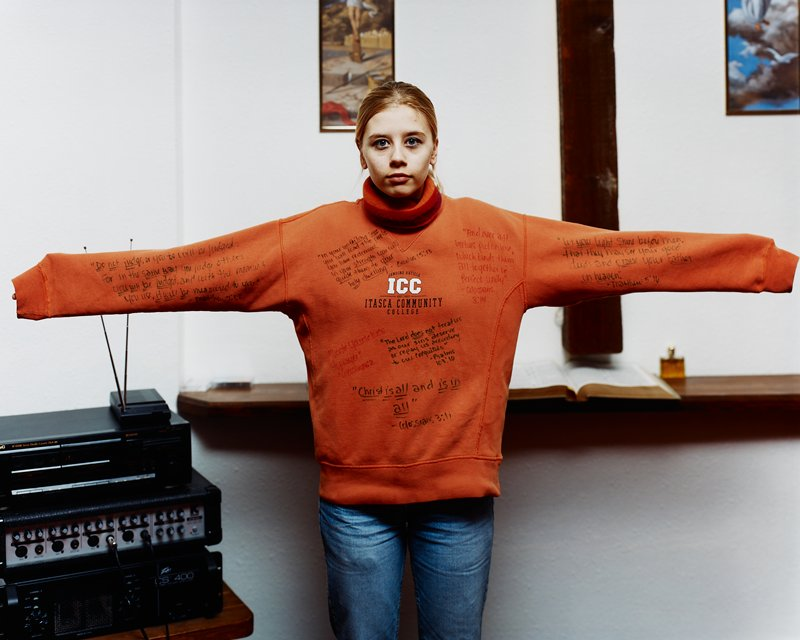young woman with arms outstretched, wearing orange sweatshirt with handwritten Bible verses; sound system at left