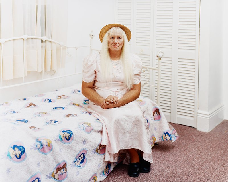 woman with long blonde hair wearing straw hat and pink dress; woman is seated on bed with Disney Princesses blanket
