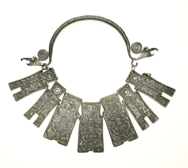 torque with seven plaques joined together with rings at top and shoulder of each plaque; neck ring wire wrap with dragon heads at each end and spiral motif at back of head; plaques are decorated with relief designs on both sides; designs are different on each side; reverse has stick figures; on front, four outer plaques have two human figures with a bird and a snake motif on each; three center plaques have writing in Asian language characters surrounded by flora and fauna; loop and hook closure at dragon's head