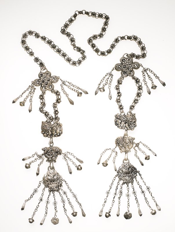 ornament with one long strand of flower chain; this chain has a large flower attached at both ends; the flower has two triangular cones and a bell dangling from chains on each side; the large flower has two flower chains dangling down; these are attached to a tiger on each side; the tiger links to a bird; the bird has two triangular cones and bell dangling from each side; the bird is attached to a floral pattern piece; this piece has seven chains with flowers in the center of the chain; four of these chains have triangular cones at the end; two chains have bells at the ends; the center chain has a flat, flower piece at the end