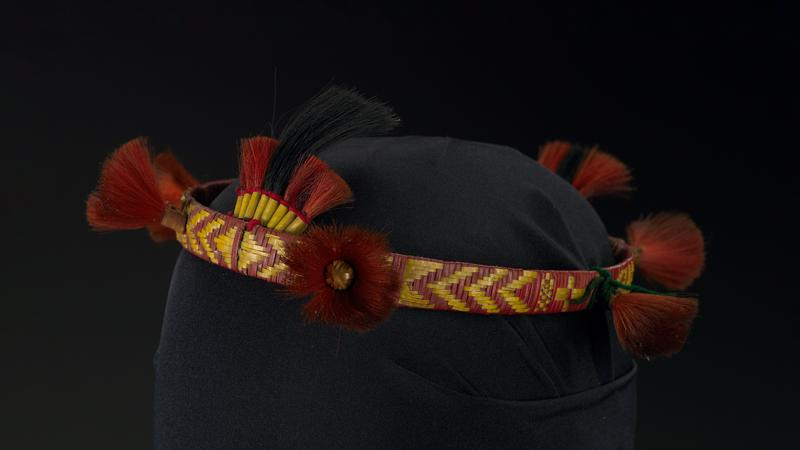 "red and yellow fibers woven around circular band; six brush-like red-orange elements; two tassel-like ornaments with red-orange and black hair, front and back; one large ""tassel"" has longer black hairs"