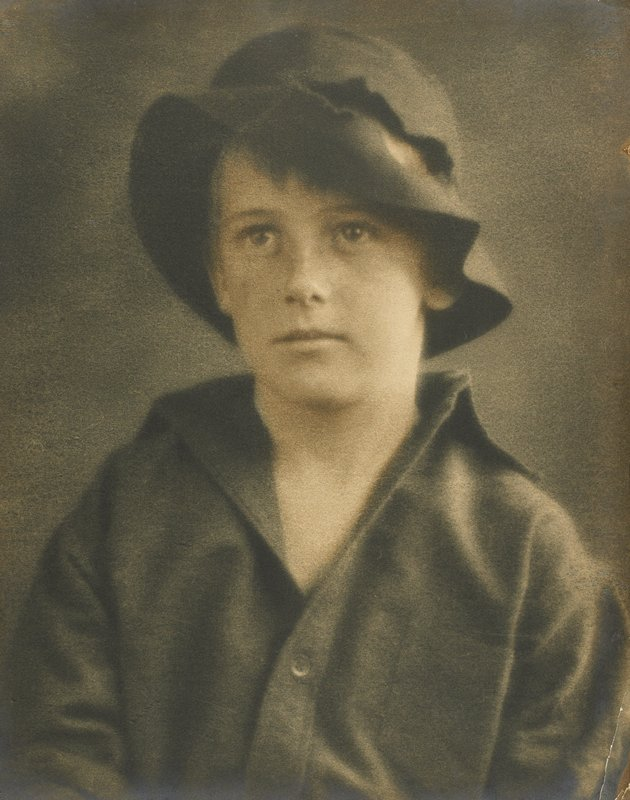 portrait of young man wearing hat with large tear on PL above rim and open neck shirt