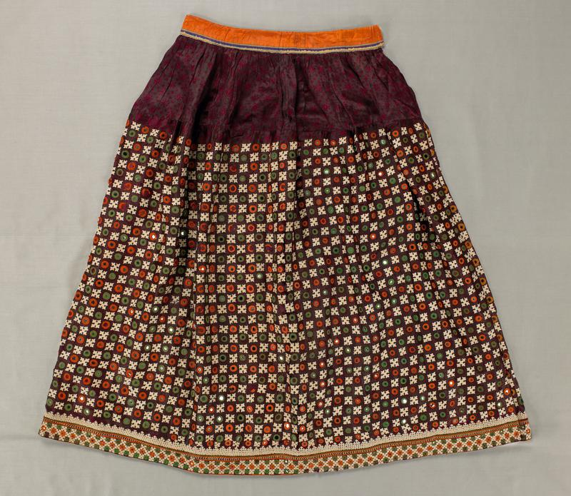brown with maroon floral shapes and circles; embroidered overall with circles with mirrors and cross shapes in white, green, and orange; orange waistband