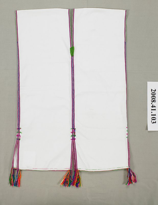 white sleeveless blouse; slits (open seam), front and back and both side seams; tassels at bottom ends of slits; reinforced with embroidery along all edges; woven stripes of yellow and purple lengthwise at edges; tape reinforcement at neckline V--red and green