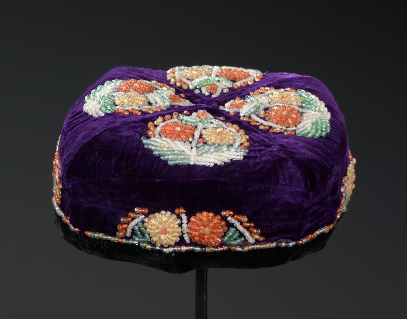 small square-shaped hat; purple velvet with black velvet trim; red lining; four beaded flower medallions on top--blue, white, green, orange, yellow; beaded flower spray on each side