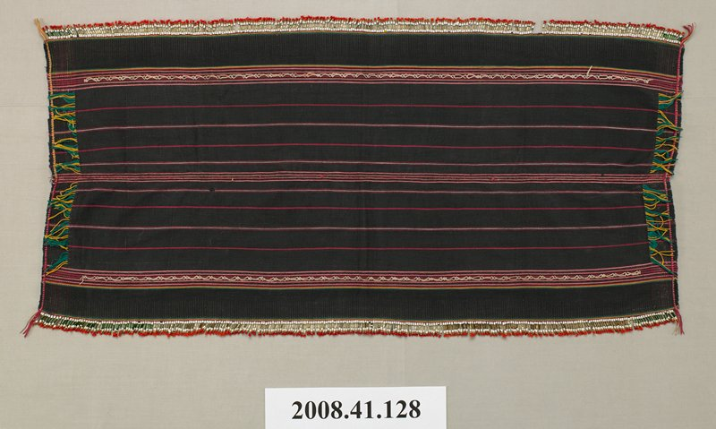 small black oblong beaded and embroidered skirt; two vertical bands at either edge and two horizontal bands near top and bottom of red, green and gold embroidery in geometric patterns; narrow embroidered vertical seam through middle; row of beads across top and bottom; top and bottom solid black panels have raised vertical lines in the fabric; thin fringe of embroidery threads at each corner
