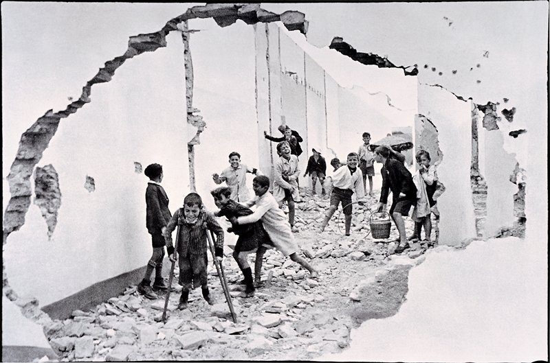 boys playing in rubble, looking through an opening in a wall