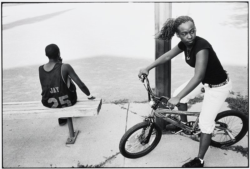 black girl wearing black T-shirt and light-colored Bermuda shorts with her hair in a ponytail seated on a bike at R; black boy, seen from back, wearing a #25 basketball jersey, seated on a bench at L
