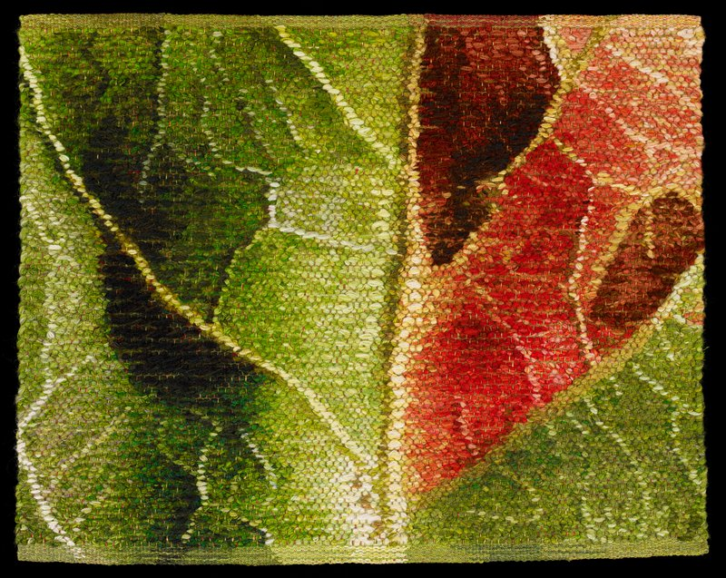 small tapestry woven in greens, reds, oranges, brown, yellows; close-up view of a leaf; attached heading band on back
