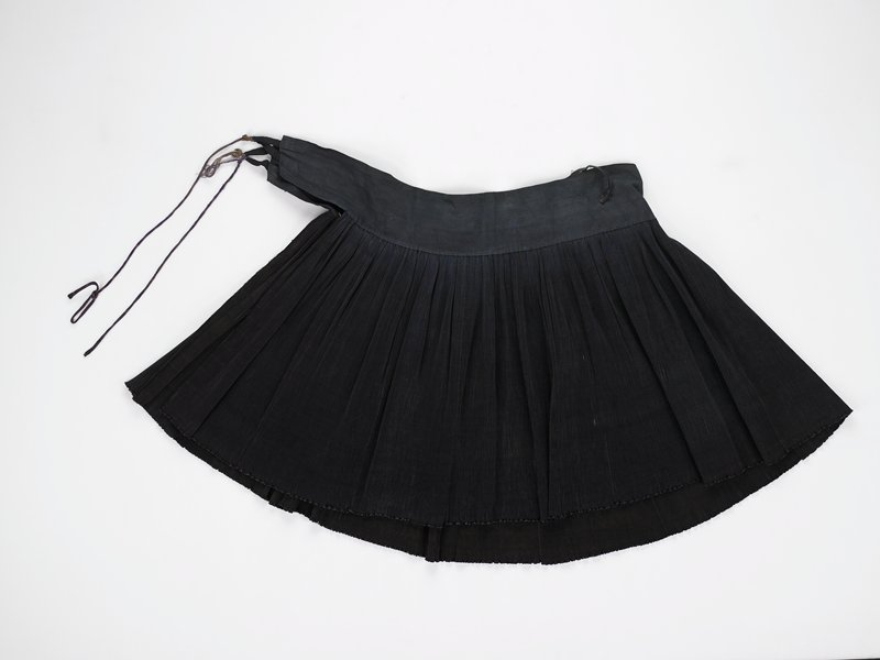 blue fine pleated skirt; subtle blue and brown stripes on one side; cord ties; black tape loop at front