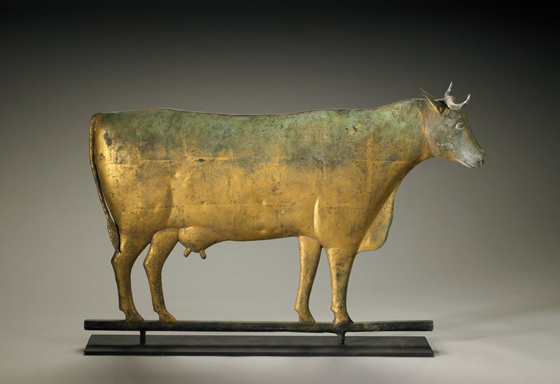 slightly rounded body with fully three-dimensional head; short horns; udder with two teats; gold, green and grey patina