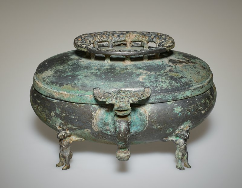 The bowl, in the broad and bulky shape of the Huai style, is supported by four human figures with horned animals' heads. The rigid ring handles have an out-curving lower projection which, with the outer bend of the ring, forms a dragon with a curled-up tail. This dragon has a head like a t'ao-t'ieh. The ring-shaped top of the lid, adorned with a triple-strand plait pattern in openwork, is affixed to the lid with a row of small props. The close affinity of this vessel to one almost exactly similar in the Royal Ontario Museum is interesting in view of the fact that the latter is known to have come from the Kin-ts'un tombs (Ca.450-230 B.C.). Patina green.