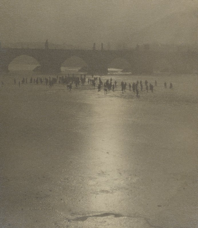bare beach in foreground; group of people at river's edge in middle ground; bridge with arches and sculptures in background; line of light down middle reflected on beach
