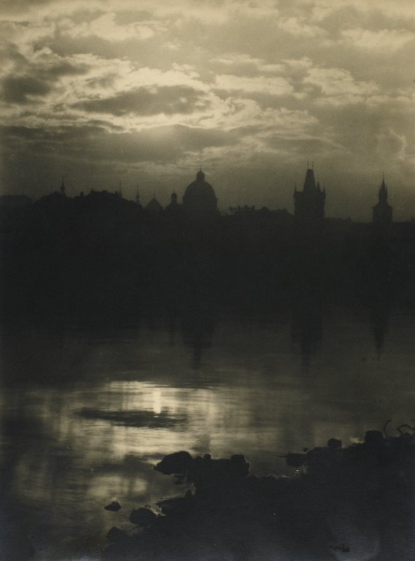 dawn or dusk with water in foreground, buildings in silhouette in background; reflection of sun in water