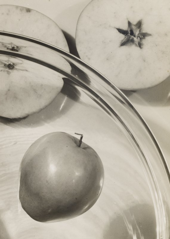 apple on clear plate in lower left quadrant and two halves of cut apple at top