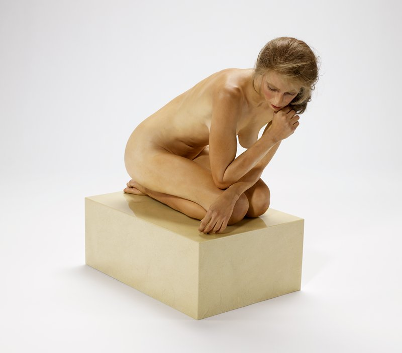 kneeling hyper-realistic life-sized nude woman, with elbows on knees and PR hand under chin, leaning forward; long blonde hair in messy ponytail; pearl earrings