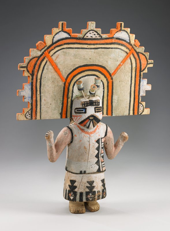 standing figure with arms bent at elbows and forearms raised; long dark hair; large flat headdress with stepped edges; three 3-D hairpins on top of heard; tunic and skirt with patterned designs; rectangular eyes; diamond-shaped mouth; brilliant orange (especially on headdress), black, peach, yellow and light blue