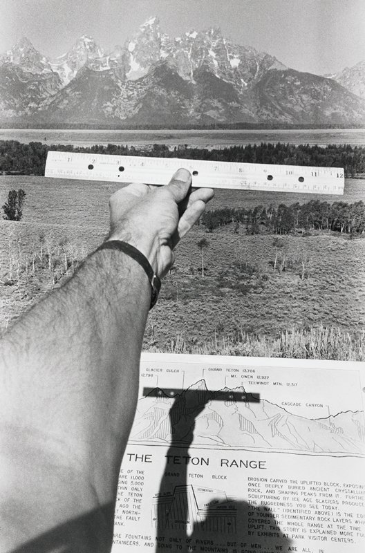 image of the Teton Mountain range in the distance with snow-covered peaks; text panel at bottom; photographer holds his PL arm out into the picture plane, holding a ruler; shadow of photographer's head, arm and ruler on text panel