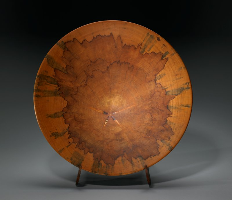 very wide, nearly platter form on ring foot; star shape in wood grain near center; brown at center with golden brown and greys at rim