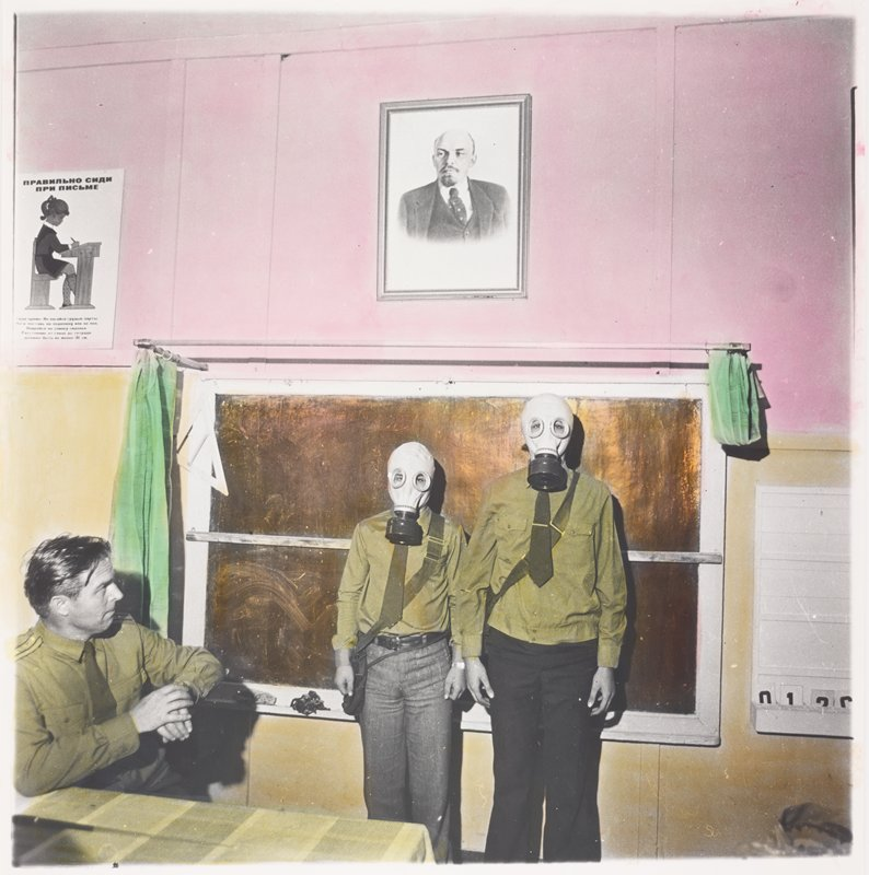 two people wearing green shirts, ties, dark pants and gas masks standing in front of a chalkboard (?) with green curtains on either side; portrait of Lenin above board; seated man at left looking at standing figures; poster with a pictures of a schoolgirl writing at a desk with Russian text at left